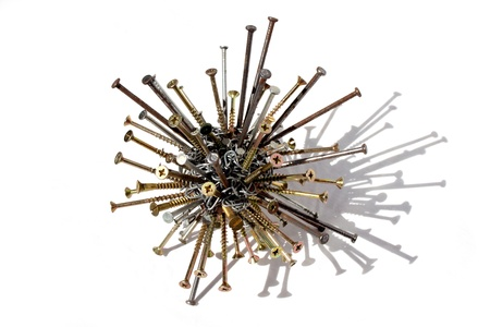 A closeup of an assembled ball of brass screws nails and tacks on an isolated white studio background photo