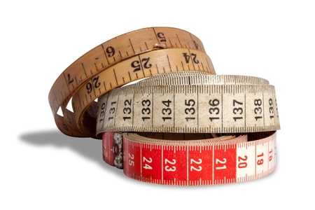 millimetres: A set of three measuring tapes ranging from new to old  on an isolated white studio background