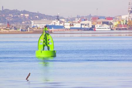 denoting: Green buoy denoting shipping lane in harbor