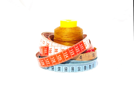millimetres: Three tape meaures coiled around roll of cotton