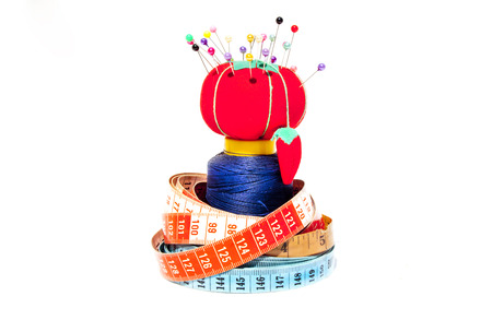 millimetres: Three tape measures coiled around roll of cotton with Pin Cushion