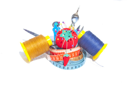 millimetres: Three measuring tapes with reels of cotton and sewing accessories