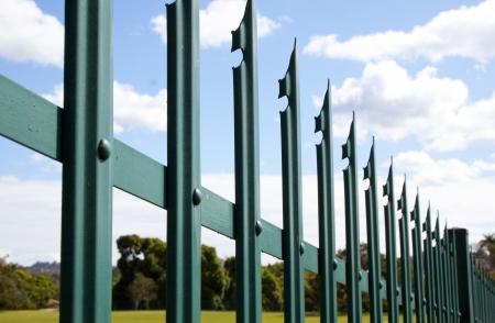 青い空と雲と緑の鋼鉄柵セキュリティ フェンスのクローズ アップ