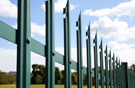 Closeup of green steel palisade security fence against blue sky and clouds Imagens - 22519594
