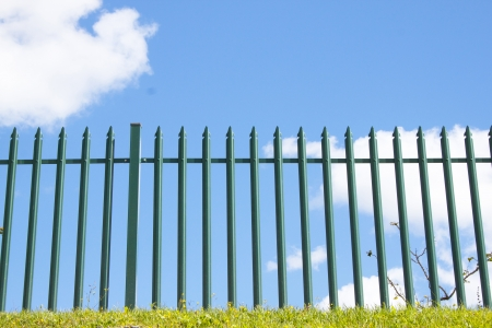 spiked: Paralell spiked green palisade fence against blue sky and clouds Stock Photo