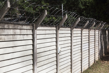 perimeter: Precast concrete wall with razor sharp security wire protecting property Stock Photo