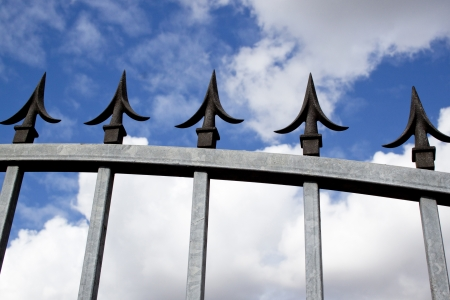 galvanised: Closeup section of steel galvanised security gate and decorative black spikes against blue sky and clouds background