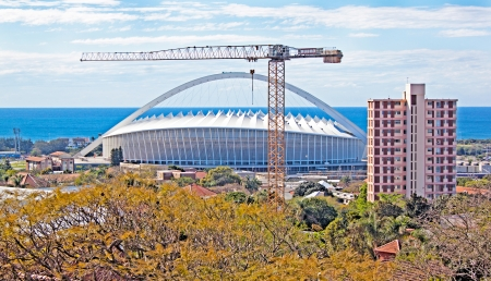 mabhida: View of Durban South Africa coastline with crane and Moses Mabhida football stadium