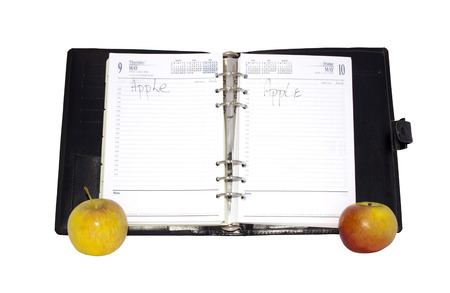 Concept photo with three red and yellow apples with an open diary depicting the saying an apple a day photo