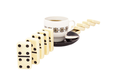 upright row: Concept photo with stacked and toppled dominoes with a cup of tea depicting a tea break