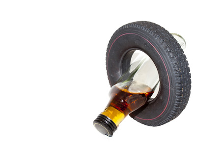 Isolated no drinking and driving concept with vertical crossed alcohol bottle and tyre photo