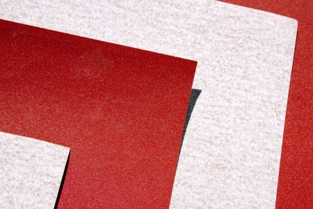 Extreme abstract closeup of texture on sheets of red and grey sandpaper