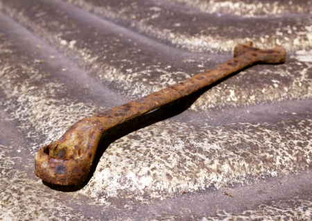 disregard: Isolated old rusted spanner on sloping textured fibreglass surface