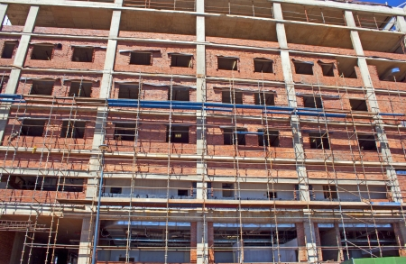 modernization: scaffolding erected around brick and concrete building under construction