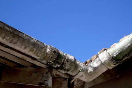 neglect: upward vew of corner of mouldy neglected asbestos guttering
