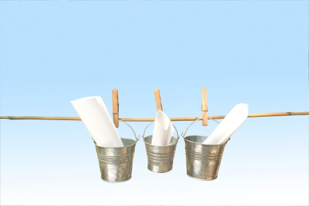 symbolization: concept three galvanised buckets pegged on bamboo stick with blue background Stock Photo
