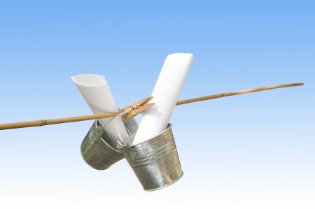 symbolization: two galvanized buckets pegged on bamboo stick with blue background Stock Photo