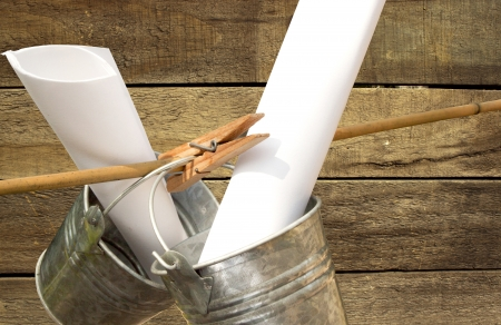 symbolization: two galvanized buckets pegged on bamboo stick with wooden slatted background Stock Photo