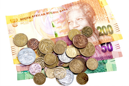 coins shot in golden color: scattered coins on three South African Rand bank notes