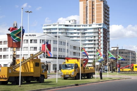 erecting: DURBAN, SOUTH AFRICA - DECEMBER 6, 2013: Municipal employees erecting South African flags at half-mast in honor of Nelson Mandela in Durban, South Africa,  December 6, 2013. Nelson Mandela, ex-president of South Africa passed away on December 5 2013 Editorial