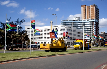 nelson mandela: DURBAN, SOUTH AFRICA - DECEMBER 6, 2013: Municipal employees erecting South African flags at half-mast in honor of Nelson Mandela in Durban, South Africa,  December 6, 2013. Nelson Mandela, ex-president of South Africa, passed away on December 5 2013