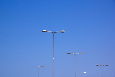 five street lamps against bright blue sky photo