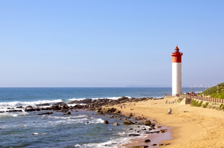 DURBAN, SOUTH AFRICA - DECEMBER 20: Umhlanga Rocks coastline with lighthouse and unknown people on beach on December 20 in Durban, South Africa Editorial
