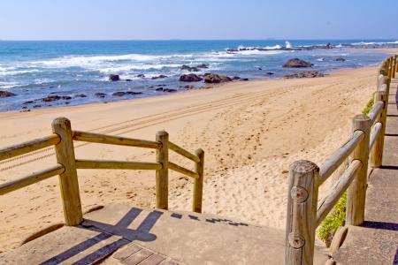 stairway with wooden handrail leading onto beach photo