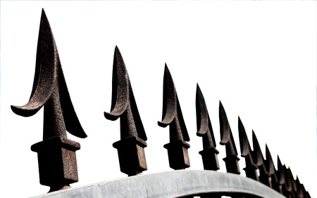 galvanised: An extreme closeup of decorative black spikes on top of galvanised security gate and frame