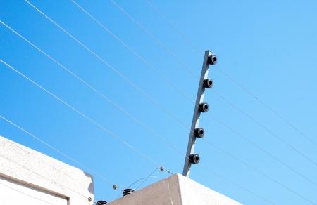 elektrizit u00e4t: Ansicht von einem elektrischen Zaun-Installation auf einer Betonwand Lizenzfreie Bilder