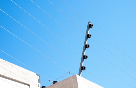 wire fence: View of an electric fence installation on a concrete wall Stock Photo