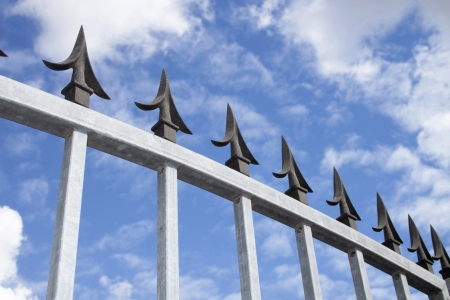 galvanised: Angled Closeup detailed view of galvanised security gate and black decorative spikes against sky and cloud  Stock Photo