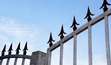 galvanised:  Coseup of decorative black spikes on top of galvanised security gate and frame