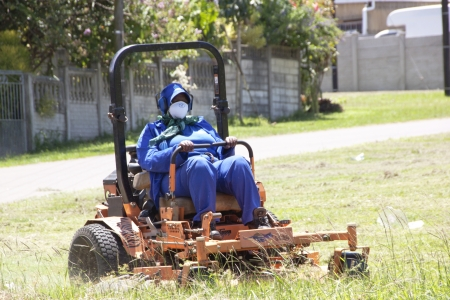 DURBAN, SOUTH AFRICA - JANUARY 23, 2014 : Unknown female municipal worker mows the grass in public park in Queensburgh Durban