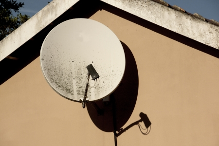 satelite: neglected dirty satelite dish mounted on wall of residnence