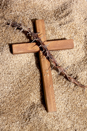 wooden cross and Christ thorn on sand