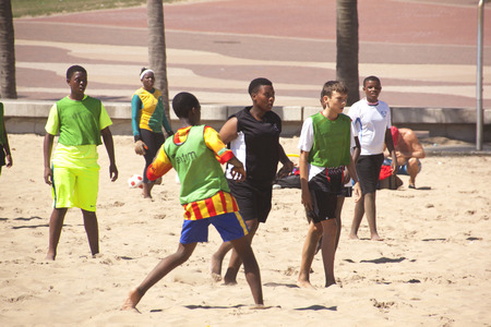 DURBAN, SOUTH AFRICA - FEBRUARY 8, 2014:  Group of male and female teenagers play football on the beach in Durban South Africa