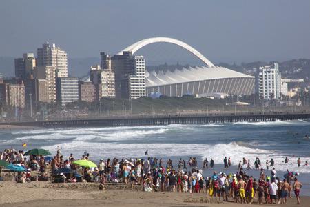 mabhida: DURBAN, SOUTH AFRICA - FERUARY 16, 2014 : Crowed gather on beach in frront of Moses Mabhida stadium in Durban South Africa,
