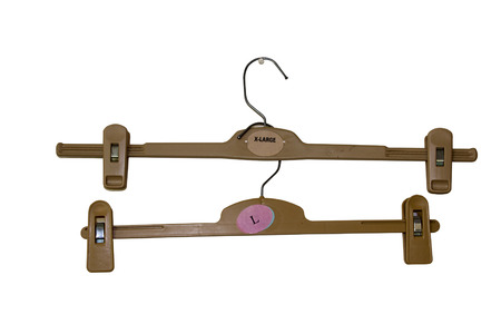 two isolated brown plastic coat hangers with built-in pegs photo