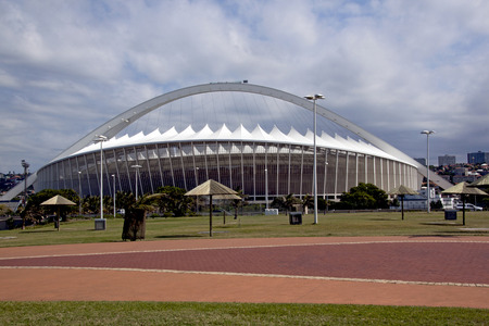 stadium  durban: DURBAN, SOUTH AFRICA - MARCH 4, 2014: Paved beachfront promenade in front of Moses Mabhida football stadium in Durban South Africa