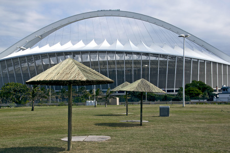 mabhida: DURBAN, SOUTH AFRICA - MARCH 4, 2014: Sunshades on grassy park in front of Moses Mabhida Football Staduim in Durban South Africa