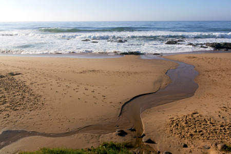 streamlet: natural streamlet running into sea at Ballito beach north of Durban South Africa Stock Photo