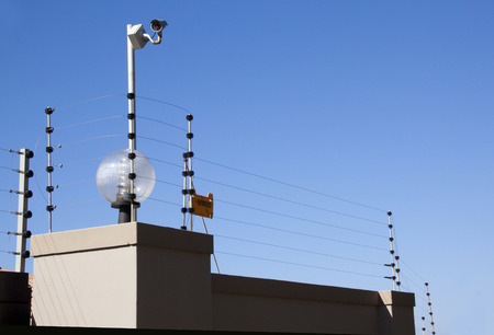 electric fence: electric fence and security camera atop boundary wall
