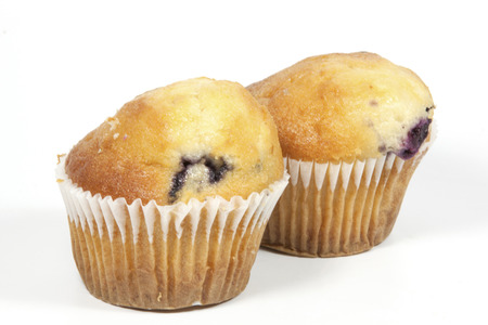 two whole blueberry muffins in cupcake cups photo
