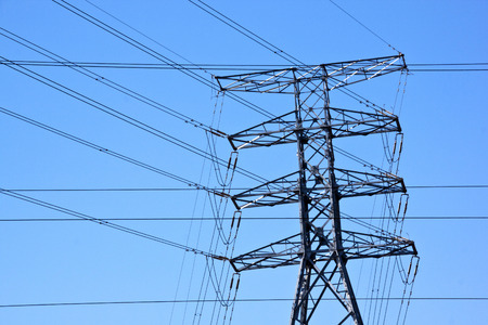 electric grid: closeup of steel pylon and cross over electric power cable grid network Stock Photo