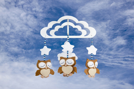 three felt owls on baby cot mobile against cloudy sky photo