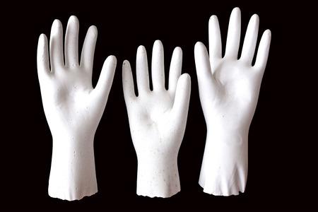 plaster of paris: three white molded raised hands on black background Stock Photo
