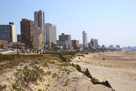 rehabilitated: DURBAN, SOUTH AFRICA - SEPTEMBER 21, 2014: Rehabilitated sand dunes and many unknown people against city skyline in Durban, South Africa