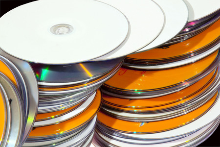 recordable media: Closeup view of a collection of many colorful stacked compact disks in a row