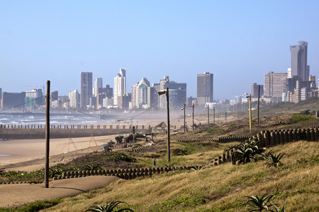 rehabilitated: Rehabilitated sand dunes against city skyline on beach front in Durban, South Africa Stock Photo